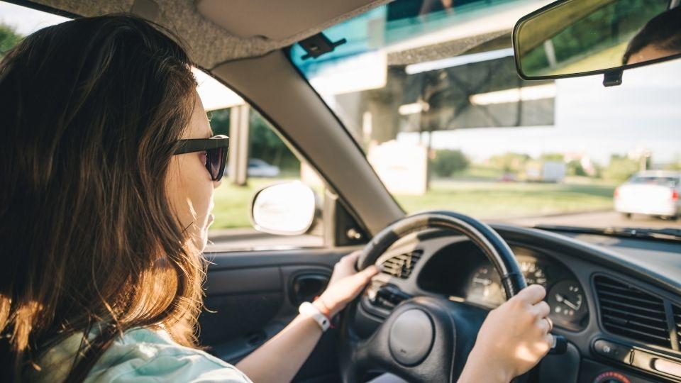 Kvinne som kjører bil som illustrasjon til artikkel om kjørebok.