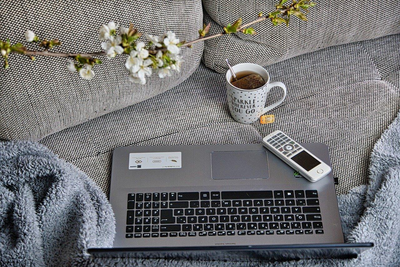 Sofa med kopp og pc, illustrasjon til artikkelen Skill privat og næring