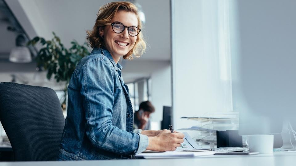Kvinne ved kontorpult, illustrasjon til artikkel om ansatt eller selvstendig næringsdrivende.