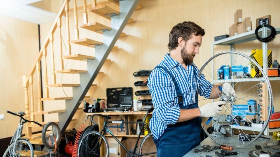 Mann reparerer sykkel, som illustrasjon ptil artikkel om å starte enkeltmannsforetak.
